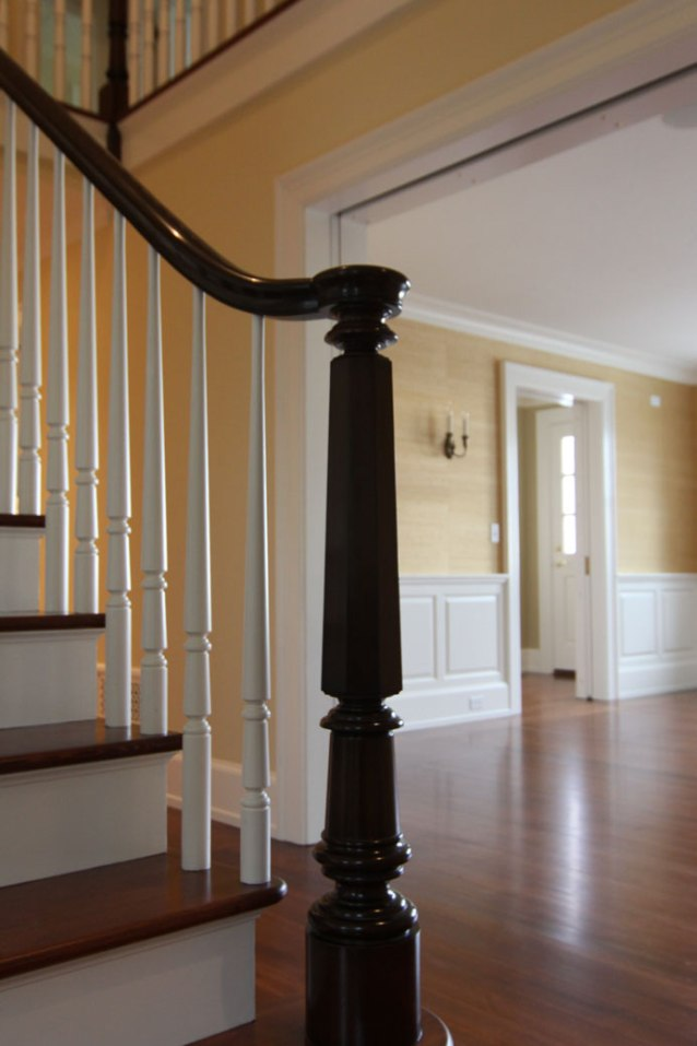 a classically inspired custom newel post and balusters provide a timeless element to this country home, all designed in collaboration with our client